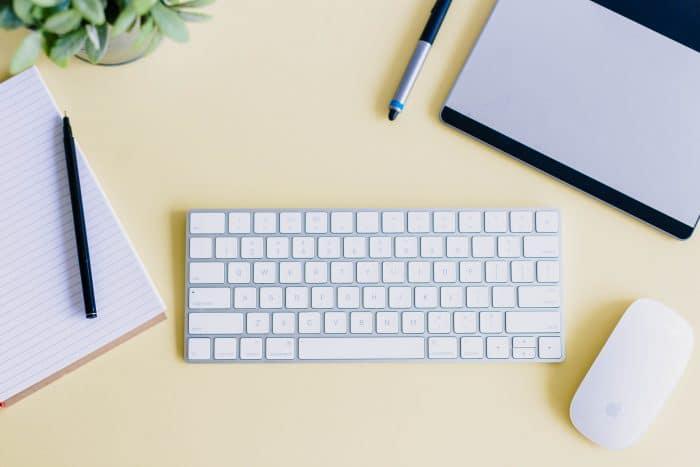 photo de bureau jaune avec clavier et souris ordinateur